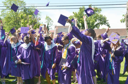 Students toss their hats in the air to celebrate.