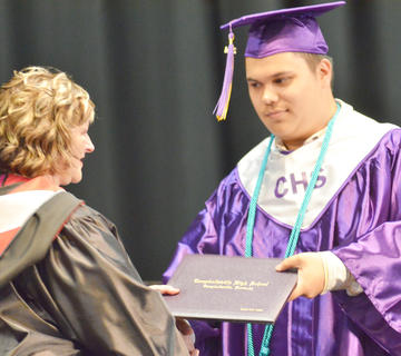 Daniel Rogers gets his diploma from Campbellsville Board of Education member Angie Johnson.