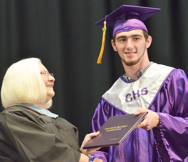 Alex Gilbert smiles as he receives his diploma from Campbellsville Board of Education Vice Chair Pat Hall.