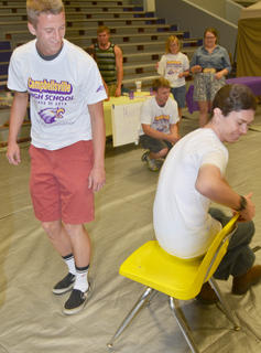 Ethan Cox smiles as he eliminates classmate Logan Dial from musical chairs at project graduation.