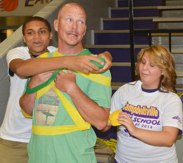Daemeunt Johnson, at left, and Katilyn Bryant wrap Chris Gupton with Mardi Gras decorations as a dare at project graduation.