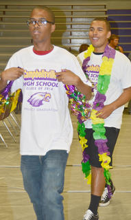 Chris Webster, at left, and D'Sean Murphy dress up and cluck like chickens as part of a dare at project graduation.