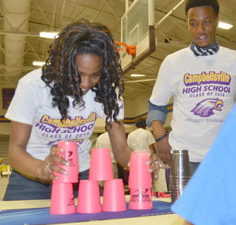 Taniesha Noyola tries to stack cups within 30 seconds to win points at project graduation.