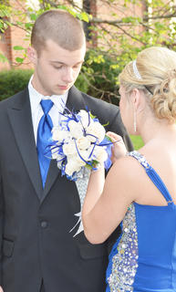 Morgan Milby adjusts Dakota Antle's boutonniere, which matched her dress and flowers, before they walk with their classmates into the CHS prom.