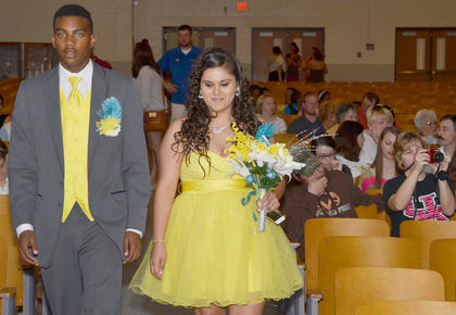 CU students Domentz Smith and Lily Delgado walk into Hamilton Auditorium at the start of their prom on Saturday night.