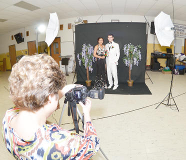 Emily Lee and Alex Gilbert smile as Valerie Davis, media specialist at CHS, takes their official prom photo.