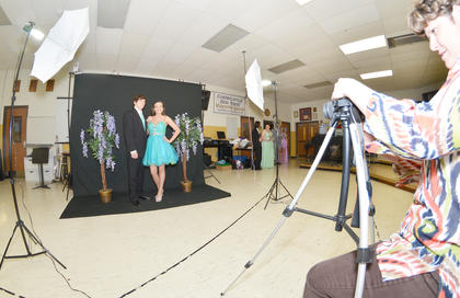 Cody Brewer and April Lotter smile as Valerie Davis, media specialist at CHS, takes their official prom photo.