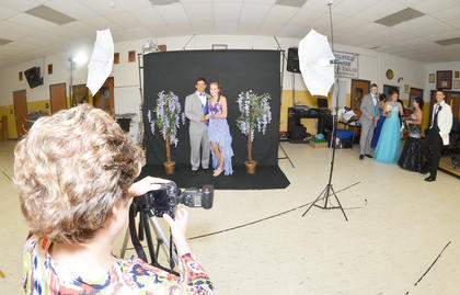 Tony Barrera and Caroline McMahan smile as Valerie Davis, media specialist at CHS, takes their official prom photo.