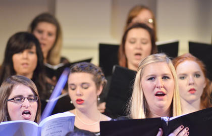 At left, Dr. April Stephens, an assistant professor of music education, sings alto with the University Chorale and Concert Chorus. At right is Sarah Harrison of Winchester, an alto, who later performed a solo.