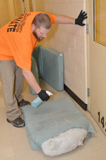 Inmate Matthew T. Nichols cleans a mat after a fellow inmate is released from the detention center.