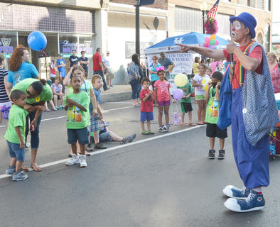 Children laugh as Cambo the Clown does tricks on the children's stage.