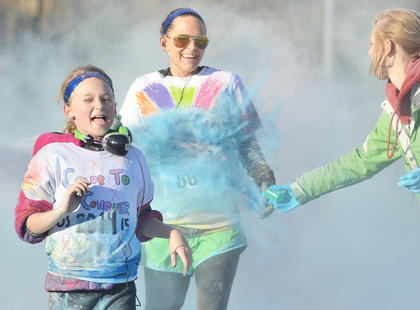 They made a splash, literally and figuratively. Though participation was down compared to last year, this year's Color to Conquer event was a success, with about 200 people running and walking to raise money for childhood cancer research. And they got a bit of color, too, when they were splashed with colored cornstarch. Above, Hailey Crosby, at left, and Jennifer Cox are splashed as they finish the Color to Conquer race. Crosby's aunt has colon cancer, and the two ran in her honor.