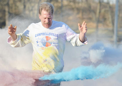 Mark Johnson is splashed as he completes this year's Color to Conquer race.