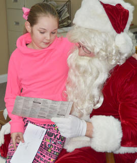 Santa tells Piper Maggard that he likes the drawing she colored for him. Maggard's entry in the coloring contest earned her a runner-up prize.