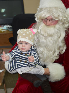 Elaine Cook, 17 months, wasn't so sure about sitting in Santa's lap, but was happy to get a candy cane.