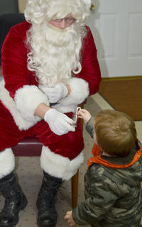 Wyatt Roby, 1, gets a candy cane from Santa.