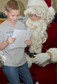 Children came to the News-Journal on Thursday to have a one-on-one visit and eat cookies with Santa. Santa also had prizes for the winners of the News-Journal's annual coloring and letter-writing contests. Above, Jesse King, who won second place in the letter-writing contest, reads his letter to Santa.