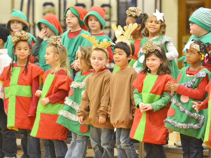 "Kindergarteners, dressed as reindeer, presents, snowmen, elves and Christmas trees, sing ""The Snowman."""