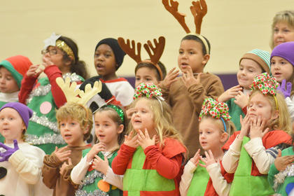 "Kindergarteners, dressed as reindeer, presents, snowmen, elves and Christmas trees, sing ""Countdown to Christmas."""