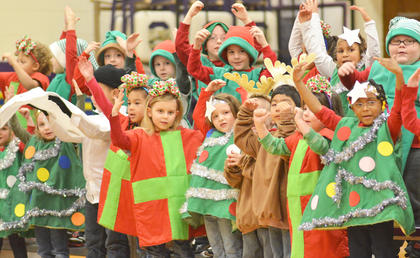 "Kindergarteners, dressed as reindeer, presents, snowmen, elves and Christmas trees, sing ""Must Be Santa"" as they describe what he looks like."