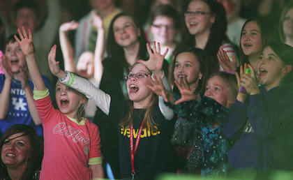 Some young fans are excited as Sanctus Real drum sticks are tossed into the crowd.
