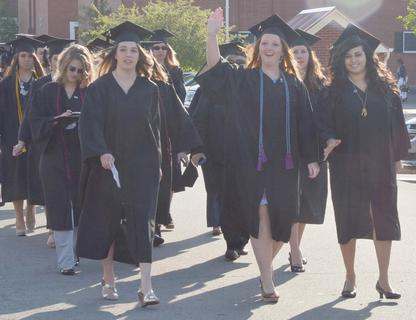 Chasity Ballard of Campbellsville, who received a Bachelor of Science degree in elementary education, waves as she and her fellow graduates participate in the Graduate Walk, the last time they will walk across the CU campus as students.