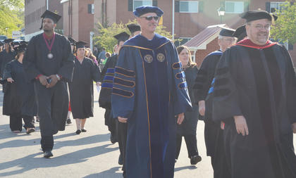 Graduates and faculty members participate in the Graduate Walk, the last time they will walk across the CU campus as students.
