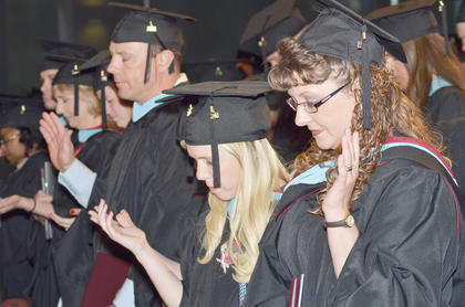 Master's graduates pray after their ceremony.