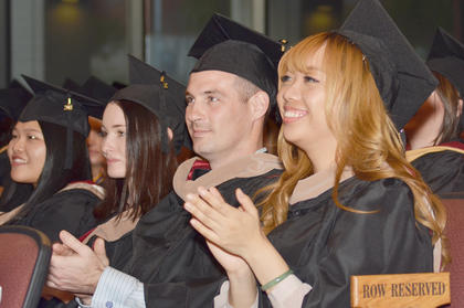 Master's students clap as their fellow graduates receive their degrees.