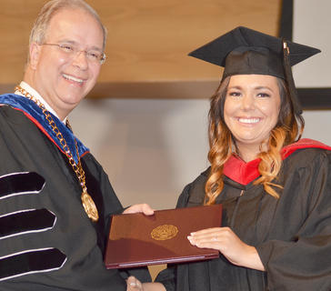 Melissa Goble smiles as she receives her Master of Theology degree from CU President Dr. Michael V. Carter.