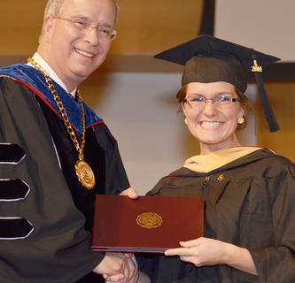 Rachel Moran of Campbellsville smiles as she receives her Master of Social Work degree on Friday night from CU President Dr. Michael V. Carter.