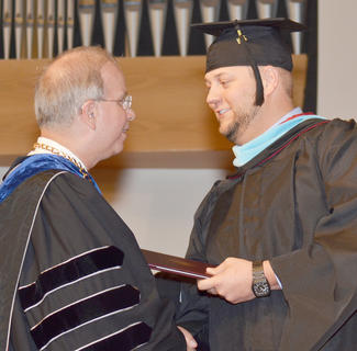 Matt Payton of Campbellsville receives congratulations from CU President Dr. Michael V. Carter as he receives his Master of Arts in Special Education degree.