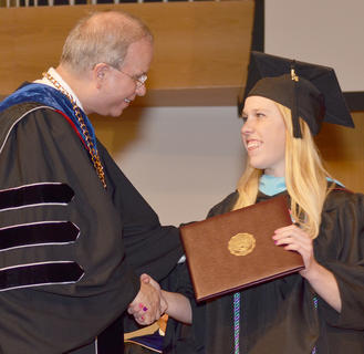 Casey Young of Campbellsville receives congratulations from CU President Dr. Michael V. Carter as she receives her Master of Arts in Social Science degree.
