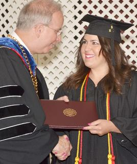 Jessie Rae Harden of Campbellsville smiles as she receives her Bachelor of Arts degree in Spanish and sociology from CU President Dr. Michael V. Carter.