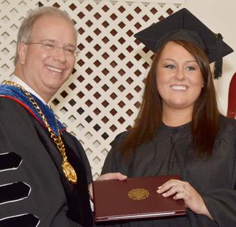 MeLeigha Pollock of Campbellsville smiles as she receives her Bachelor of Science degree in biology from CU President Dr. Michael V. Carter.