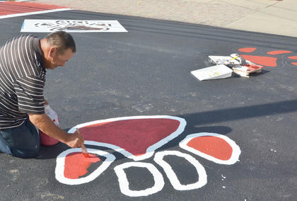 Joe Kearney, who was an art major while attending CU, paints a tiger paw maroon near the entrance to Winters Dining Hall.