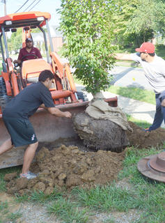 CU students Jose Cicin, at left, and David Torres work with a grounds crew to plant trees on campus. Manning the heavy equipment is Elvin AlFaro.