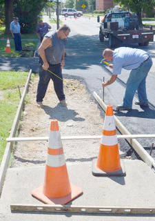 City street department workers work to make new sidewalks near the entrance to Winters Dining Hall.