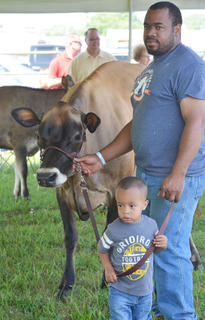 Chris Thomas and his son, Braxton, 2, of Hodgenville, formerly of Campbellsville, show their entry in the dairy show.