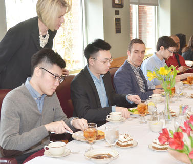 Terri Thompson of The Etiquette Edge in Paris, Ky., checks to see if students, from left, Zhi Zhou, Song Zhang, Jonathan Pufal and Jared Nolan can cut their meat correctly.