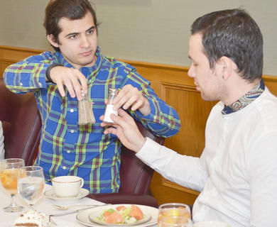 Students Maurizio Colonna and Juan Naveda learn the proper way to pass the salt and pepper during a meal.