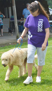 Denise Acree of Campbellsville walks her dog Butter around the track at the Taylor County SPCA's annual dog show on Sunday.
