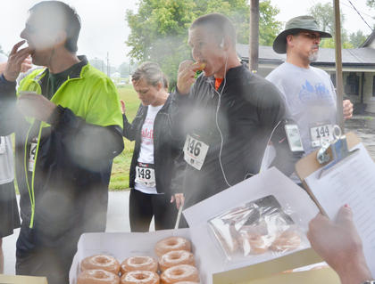 Runners take a break from the race and eat some donuts.