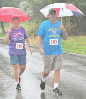 Sandy and Stephen Girard carry umbrellas as they walk in Saturday's Donut Dash.