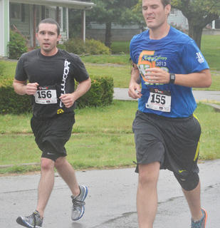 Runners Neil Hooper, at left, and Joseph Mattingly near the finish line.