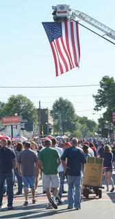 Campbellsville Fire & Rescue employees hung their large American flag over the July Fourth festivities on Main Street.