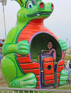 Natalie Fox smiles while sitting inside a rotating dragon.