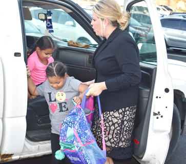 Campbellsville Elementary School Principal Elisha Rhodes helps students out of a vehicle on the first day of school.