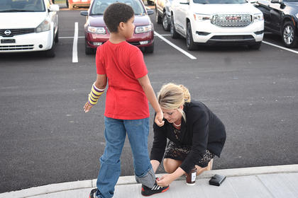 Campbellsville Elementary School Principal Elisha Rhodes helps a student tie his shoe on the first day of school.
