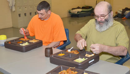 Inmates Neal Upchurch, at left, and Larry Sherrill eat lunch. Today, the lunch consists of spaghetti with meatballs, bread, salad and a dessert.